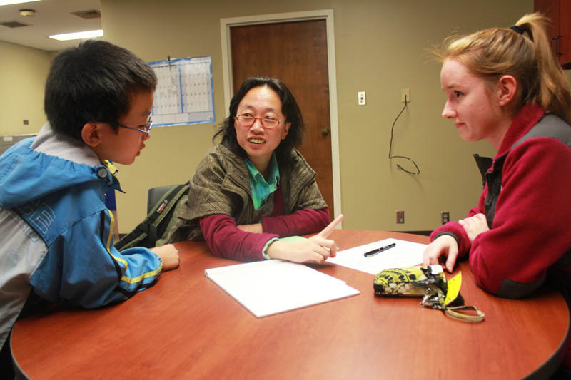 Tera Johnson, CCBP work study student, talks with Donghui Feng, a visiting scholar from China, and her son during the Global Cafe opening program.