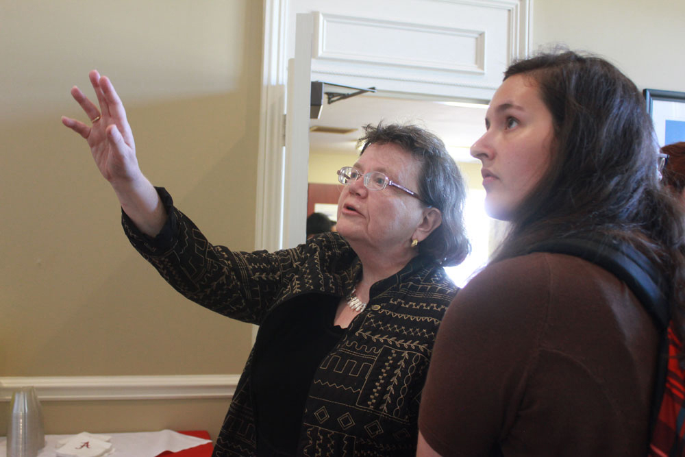 Dr. Beverly Hawk points to some of the photos that highlight the work of CCBP to UA student Ruth Bishop.