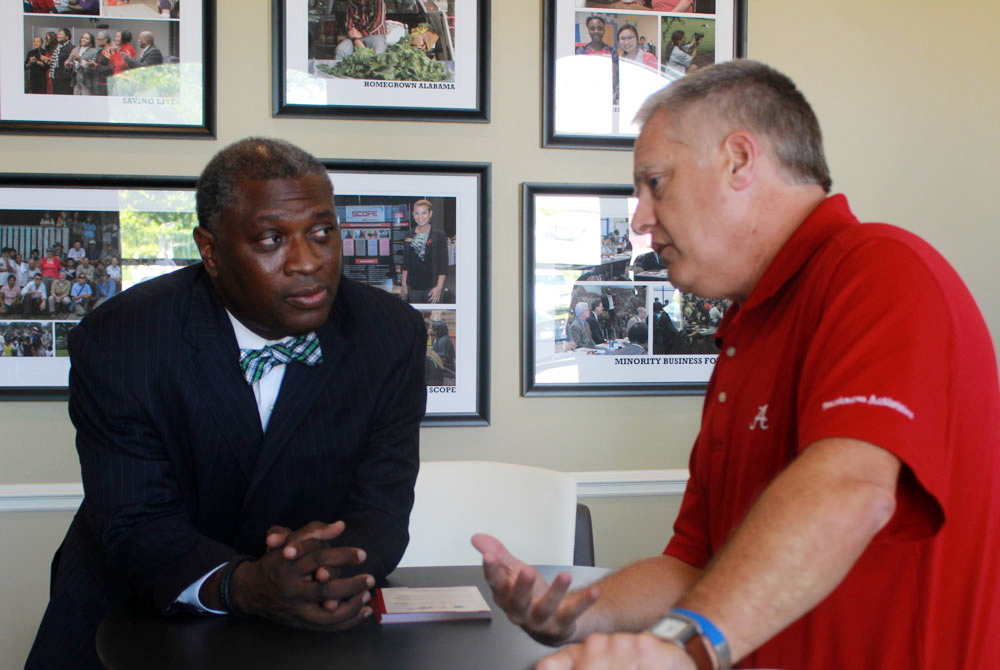 Dr. Samory T. Pruitt, left, and Mike Morrow discuss improvements at the CCBP office building during the Global Cafe/Fulbright reception. In the background are new photos documenting CCBP engaged scholarship projects.