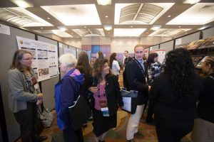 Delegates gather around research posters at the Omaha conference.