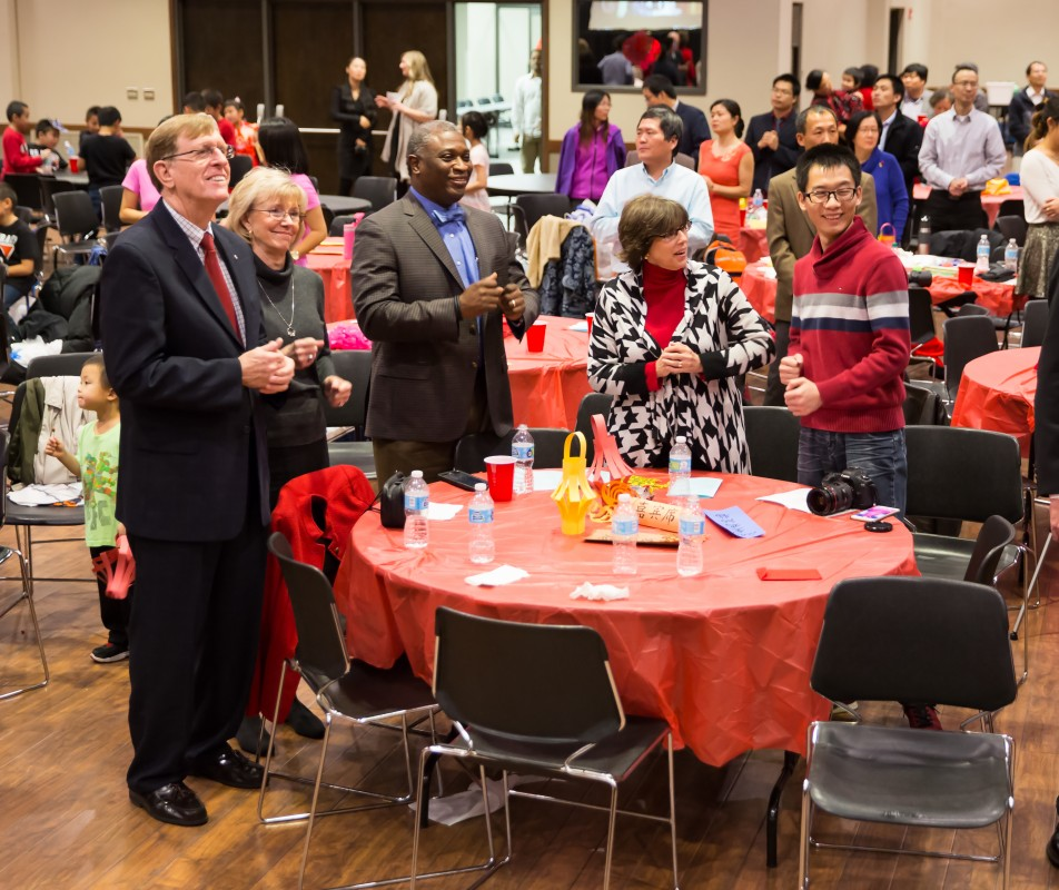 Attendees follow along with the Chinese New Year performers. From left, Dr. Jim McLean, Sharon McLean, Dr. Samory T. Pruitt, Lane McLelland and Jianlong Yang.