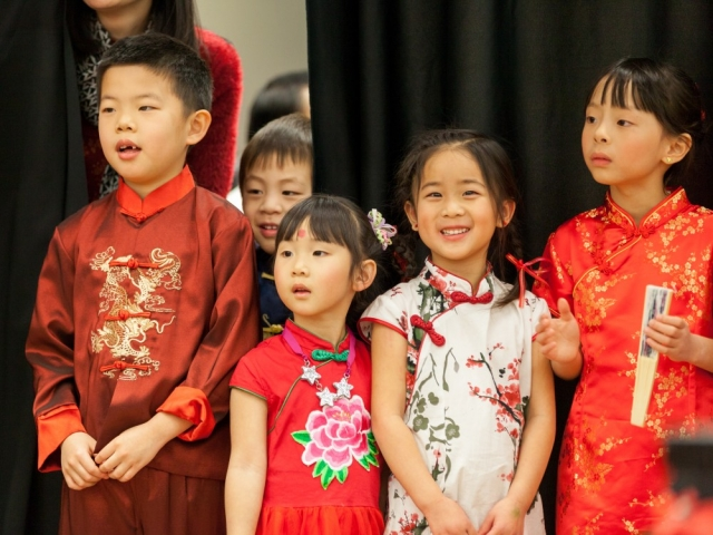 As they await their turn to perform, these children watch the Dragon Dance.