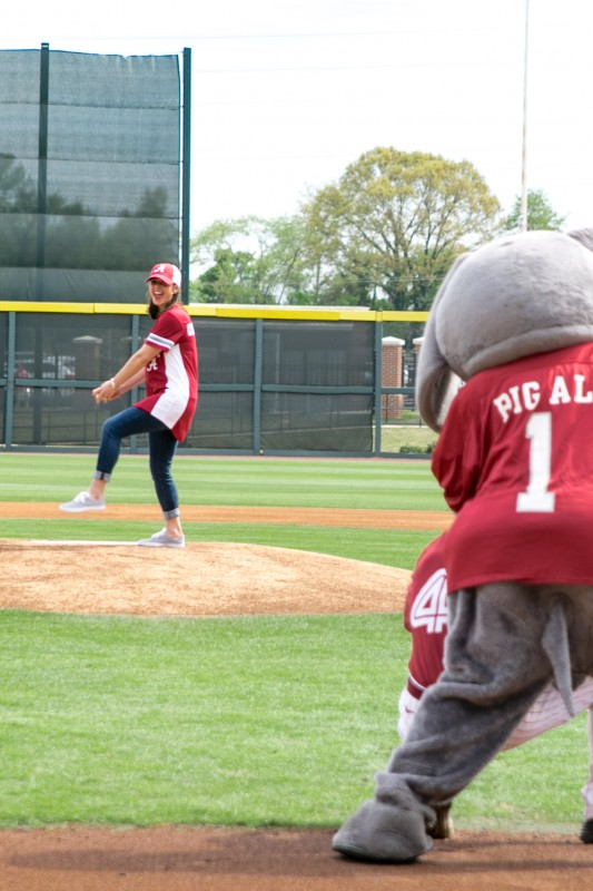 Katie Boyd Britt, president of the BOA Executive Committee, winds up to make her pitch at UA's Sunday afternoon baseball game, with Big Al looking on as umpire.