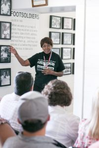 The University of Alabama's inaugural Community Engagement tour for new faculty, staff, students and community members and partners is taking place May 10–12 across nine Alabama counties. Here, on day one, legendary Civil Rights activist Theresa Burroughs speaks to tour participants at The Safe House Black History Museum in Greensboro. Designed to serve as a source of inspiration for individuals to connect research passions to addressing community needs through new partnerships, the tour is hosted by the UA Division of Community Affairs, in partnership with the Office of Academic Affairs, the Graduate School, the Center for Community-Based Partnerships and the Council on Community-Based Partnerships.