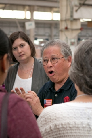 KC Pang, a former UAB professor who now serves as director of Human Resources and Corporate Affairs for GD Copper USA, Inc., speaks to tour participants inside the Golden Dragon Plant, which manufactures pipes that are used in air conditioner machinery.
